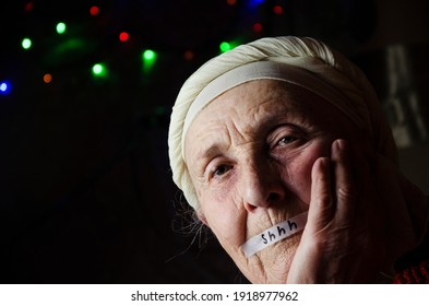 Silence. A portrait photo of a grandmother with her mouth sealed. Help me. Grandma asks for help. Inscription help me. Limitation of human rights. Restriction of human freedom. Forced silence.