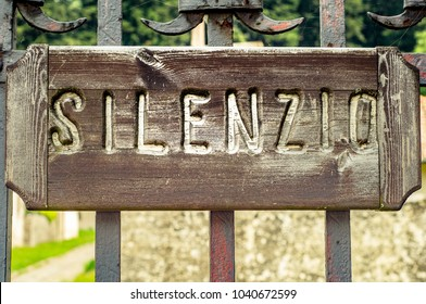 Silence sign. Carved wood sign posted on iron gate. Italian language.