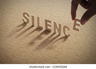 SILENCE wood word on compressed or corkboard with human's finger at E letter.