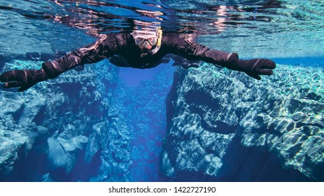 Silfra, Thingvellir National park / Iceland - June 10 2019 Tourists people snorkeling in famous popular fissure drift crack Silfra between tectonic plates in crystal clear cold glacial water dry suit