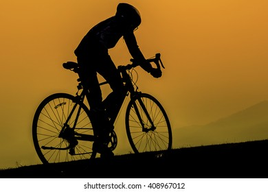 silhoette of a biker in sunset. Using a concept of exercise and