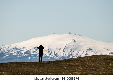 Silhoette of a man looking at scenic Snaefellsjokull mountain covered by snow