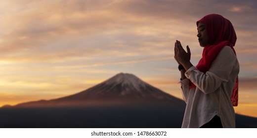 Silhoueitte of young muslim woman pray with beautiful sunset/ sunrise in background of Fuji mount