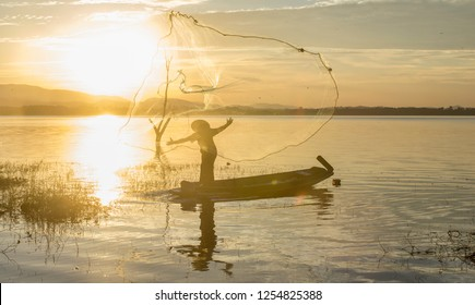 Silhouelte of fisherman on wooden boat,Fisherman in action catching in nature rive on sunrise