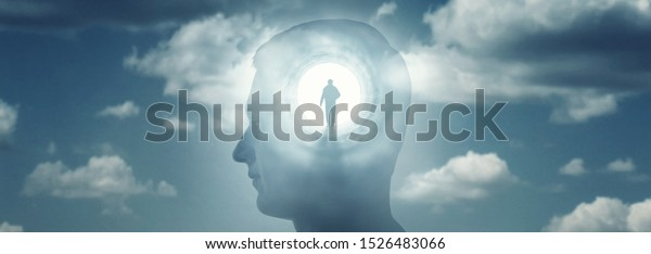 A silhouete of a man with rays of light emanating from the brain as a symbol of the power of thinking. Concept on the topic of psychiatry (bipolar disorder, schizophrenia), psychology, religion.
