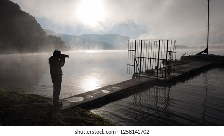 Silhouete of a man taking phot of the pier in a lake in a misty