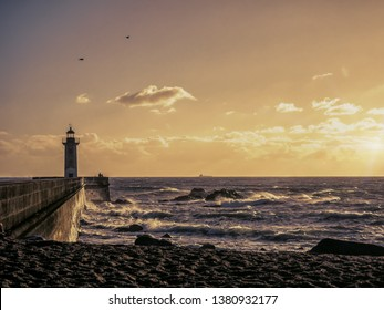 Silhouette of 19th century hexagonal lighthouse on the Douro River against the sunset sky, Porto, Portugal