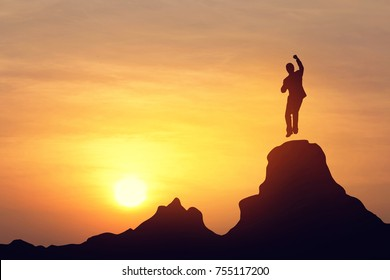 Silhouette achievements successful jumping and arm up on top mountain. A man is celebrating success with sunrise. Vintage filter.