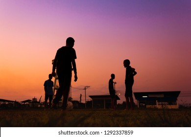 Silhouette action sport outdoors of a group of kids having fun playing soccer football for exercise in community rural area under the twilight sunset sky.