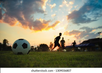 Silhouette action sport outdoors of a group of kids having fun playing soccer football on green grass field for exercise in community rural area under the twilight sunset sky.