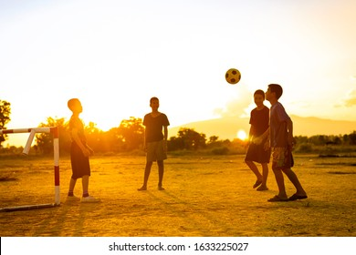 Silhouette action sport outdoors of a group of kids having fun playing soccer football for exercise in community rural area under the twilight sunset. Poor and poverty children in development country.