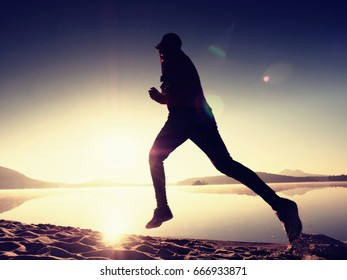 Silhouette of active athlete runner running on sunrise shore. Morning healthy lifestyle exercise on sandy beach.  Man long jumping at ocean,  sprinting with high  energy in outdoor cardio training .