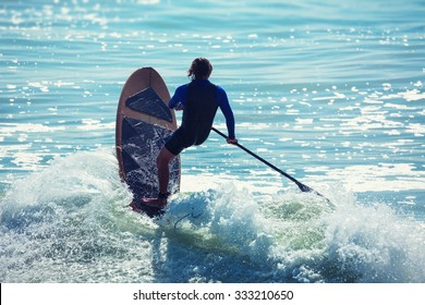 Silhouette of active surfer on paddle board surfing in ocean.