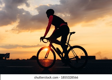 Silhouette of active young cyclist on protective helmet biking on road during evening time. Beautiful sunset on background.