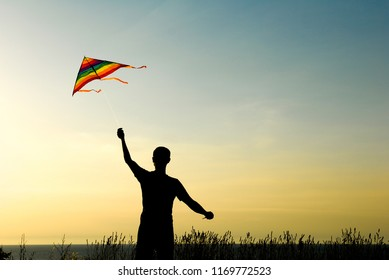 silhouette of active young man playing with flying kite outdoors in warm sunset