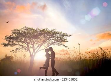 Silhouette Adam and Eve on Eden garden background.