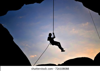 Silhouette of an adventurous lady falling by rope from a rocky mountain