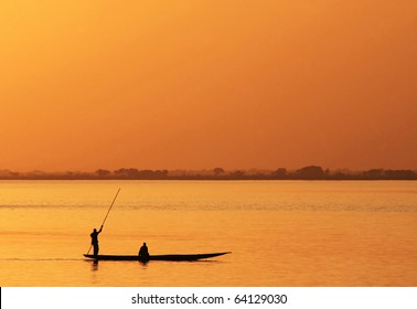 Silhouette of African fisherman in canoe at sunset