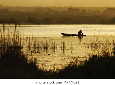Silhouette of an African fisherman on a lake