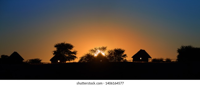 Silhouette of african village on horizon against morning orange-blue sky and rising sun. Calm african landscape, Kalahari, Botswana.