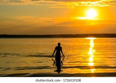 Silhouette against the background of an orange sunset on the famous lake Krasavitsa in Zelenogorsk