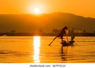 Silhouette against the morning light fishing Inle Lake, Myanmar.