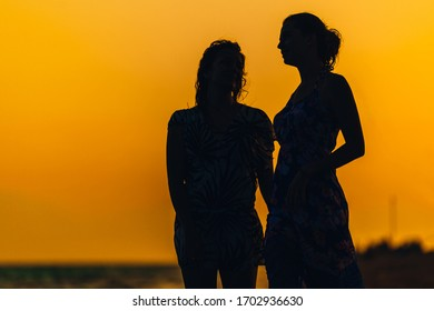 Silhouette against the sea sunset. Girsl on the beach relaxing in the evening