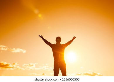 silhouette against the sky with hands up symbolizing freedom. business success concept. achievements in sports and yoga.