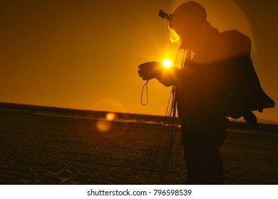 Silhouette against the sun of a skydiver figure standing in the field after a parachute jump close-up. Picture in warm colors through an orange filter. Parachute jumps.