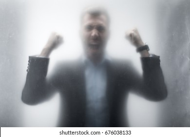 Silhouette of aggressive businessman in suit screaming behind the glass