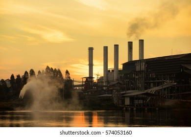 silhouette agroindustry factory during sunrise, beauty in nature factory with smog on orange sky background