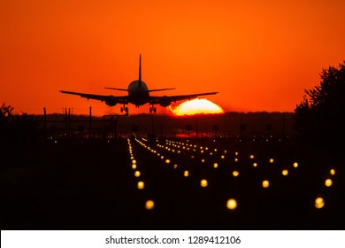 Silhouette of air plane landing on illuminated track at sunset with beautiful red sky and sun in background