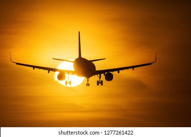 Silhouette of an air plane over the sun with beautiful red clouds in background