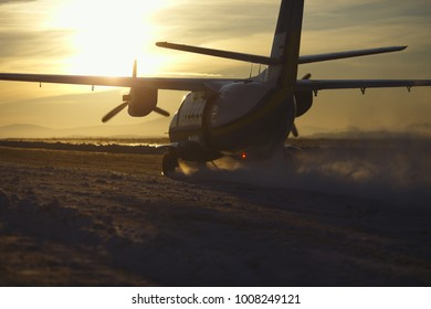 Silhouette aircraft against the sun during accelerated runway before take-off.