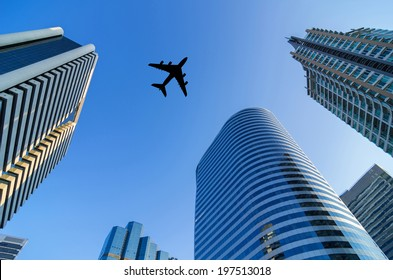 Silhouette aircraft flying over modern building in the business district.