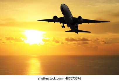 silhouette Airplane fly above sea at sunset - Travel Concept