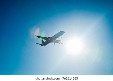 Silhouette of airplane flying against bright sun