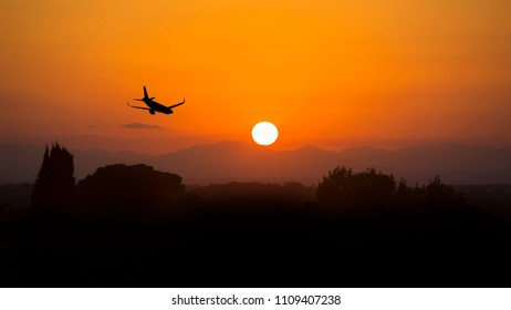 Silhouette airplane flying on the sky at sunset