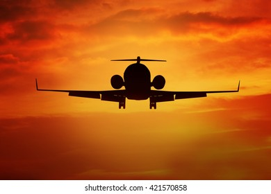 Silhouette of airplane flying on the sky with orange color, shot at dusk time