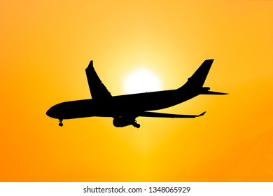 Silhouette airplane flying on sunset and prepare for landing, concept of travel