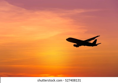 Silhouette airplane flying on sunset