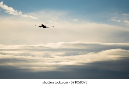Silhouette airplane flying in the sky surround by blue cloud