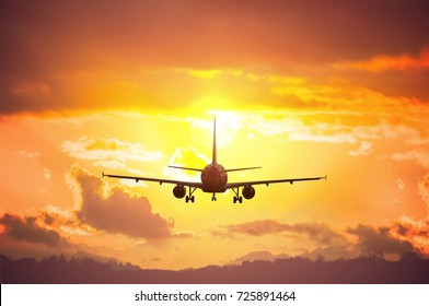 Silhouette of airplane flying in sunset.