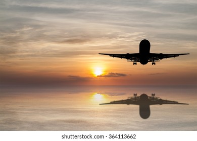 Silhouette of Airplane flying tropical sea at sunset time with reflection.