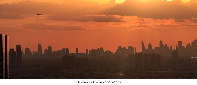 silhouette airplane flying twilight sky over bangkok city, thailand