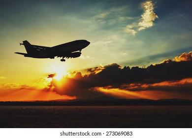 Silhouette of an airplane landing. Beautiful sunset evening sky.
