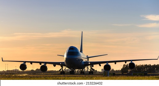 Silhouette of airplane at sunset, front wingspan