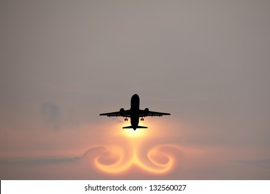 Silhouette of an airplane taking off creating a surreal turbulence jet-stream against a surreal fiery sun.