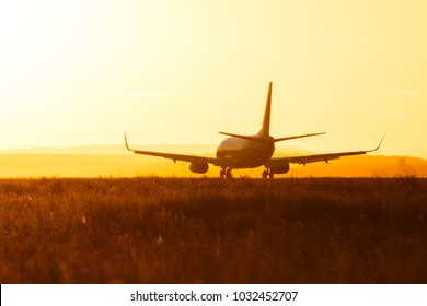 Silhouette of an airplane taking off during sunset