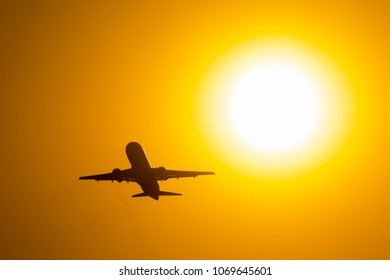 Silhouette of airplane taking off during sunset, flies near the disc of the sun